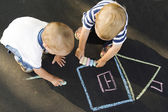 Two boys drawing house on asphalt — Stock Photo