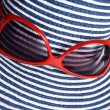 Closeup of striped hat and red sunglasses — Stock Photo