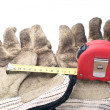 Retractable steel tape and work gloves. — Stock Photo