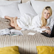 Woman Lying on Bed Using Laptop - Stock Photo