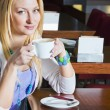 Stock Photo: Young Woman Drinking Coffee in Cafe
