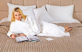 Woman Lying on Bed reading magazine — Stock Photo