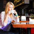 Foto Stock: Young Woman Drinking Coffee in Cafe