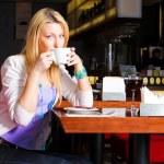 ung kvinna dricker kaffe i caféet — Stockfoto