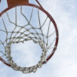 Foto Stock: Orange basketball hoop against blue sky