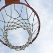 图库照片: Orange basketball hoop against blue sky