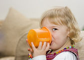Toddler girl drinking from a cup — Stock Photo