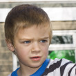 Candid close up portrait of a cute six year old boy looking worr — Zdjęcie stockowe