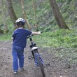 A young six year old boy pushing his bike — Stockfoto