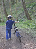 A young six year old boy pushing his bike — Stock Photo