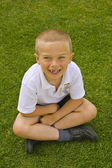 Cute six seven year old schoolboy sitting on the grass — Stock Photo
