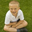 Cute six seven year old schoolboy sitting on the grass — Stock Photo #3416324