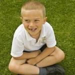 söta sex sju år gamla skolpojke sitter på gräset — Stockfoto