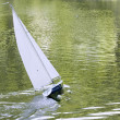 A radio control toy yacht sailing on a lake — Stock Photo