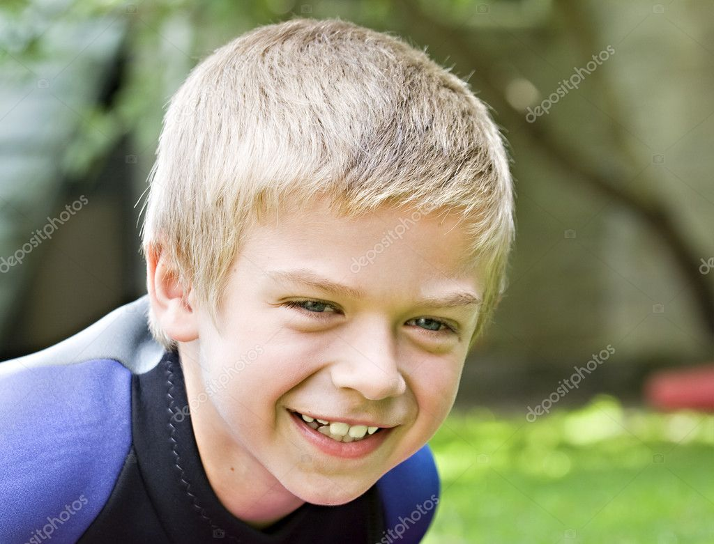 Eight year old boy smiling at the camera  Stock Photo #3499526