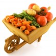 Wooden wheelbarrow with vegetables — Stock Photo
