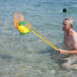 Elderly man is playing in the sea — Stock Photo