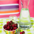 Carafe water and cherries — Stock Photo