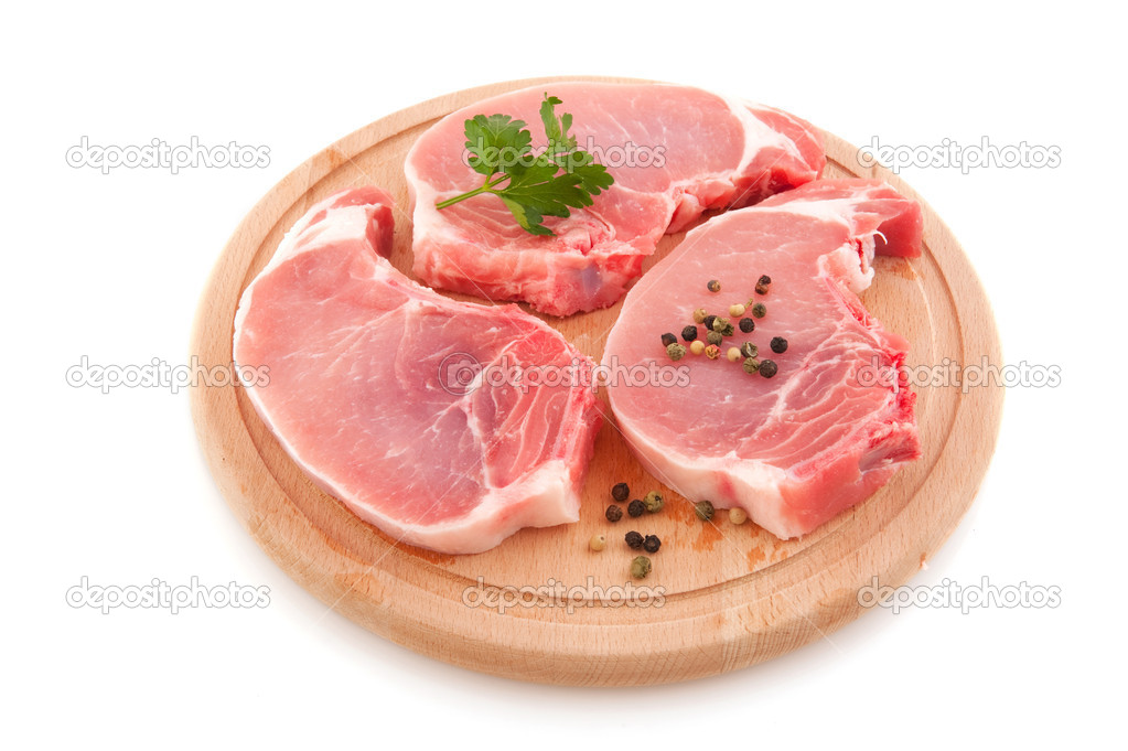 Fresh pork chops or cutlets with parsley on round wooden plate — Stock Photo #3776140