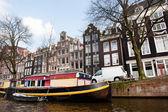 łódź dom kanałem w amsterdamie — Zdjęcie stockowe