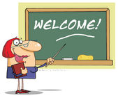 Female Teacher Pointing To A Welcome Chalkboard — Stock Photo