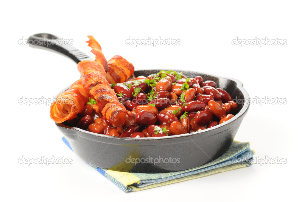 Baked beans and bacon served in a cast iron skillet.  Lizenzfreies Foto #3850207