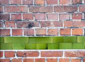Velha parede de tijolo vermelho com uma linha de telhas de esmalte verde — Foto Stock