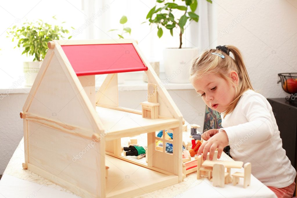 Cute little girl plays with doll's house — Stock Photo #3069508