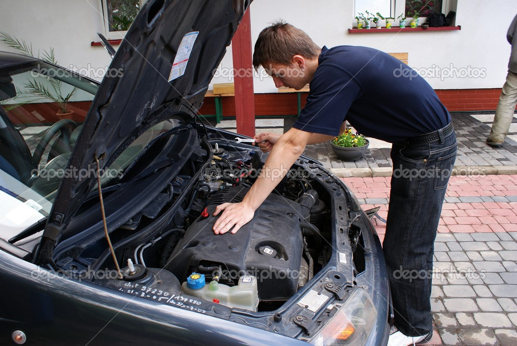 This is a car mechanic next to the engine of small city car — Stock Photo #3124045