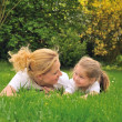 Young mother and daughter on the grass — Stock Photo