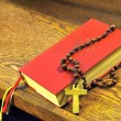 Hymnal  book and wooden rosary bead - Stock Photo