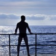 Silhouette of young man standing at the seaside — Stock Photo #3334626