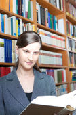 Young woman reading a book in the library — Stock Photo
