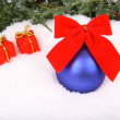 Christmas background with red present and blue ball — Stock Photo
