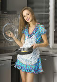 Happy housewife in the kitchen — Stock Photo