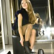 Foto Stock: Girl fits on boots in boutique