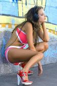 Chica en traje de baño es escuchar música — Foto de Stock