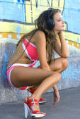Girl in bathing suit is listening music — Stockfoto