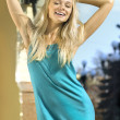 Happy blonde in turquoise dress — Stock Photo