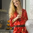 Happy blonde woman in the kitchen — Stock Photo