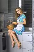 Housewife with basket in the kitchen — Stock Photo