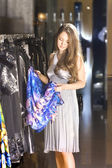 Rich woman chooses a dress in a boutique — Stock Photo