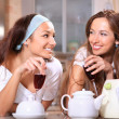 Happy women with wine in kitchen — Stock Photo