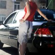 Stockfoto: Blonde woman near black automobile