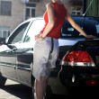 Blonde woman near black automobile — ストック写真