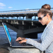 Stock Photo: Businesswomwith laptop on quay