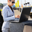Woman with computer on quay — Stock Photo