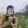 Woman blows soap bubbles — Stock Photo