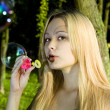 Blonde woman blowing soap bubbles — Stock Photo #3494406