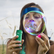 Face of woman that blows soap bubbles — Stock Photo